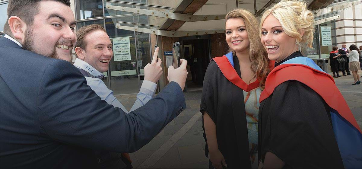 Photograph of four students at graduation smiling and taking photos of each other