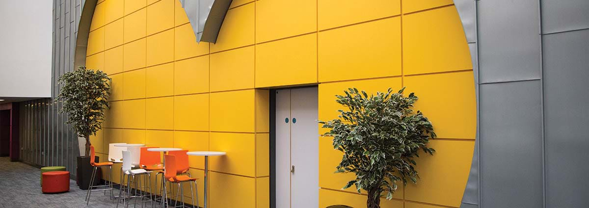 a photograph showing the inside of Space Bangor, a yellow and grey wall.