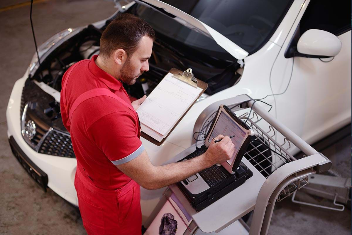 Photograph showing a male student working on a car