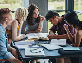 A picture of students sitting around a table helping each other study